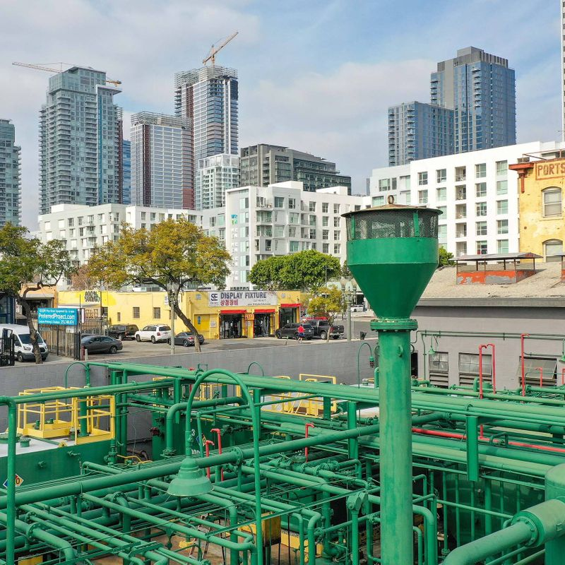 A petroleum well operation consisting of a network of green pipes, sits in the foreground of the Los Angleles downtown cityscape.