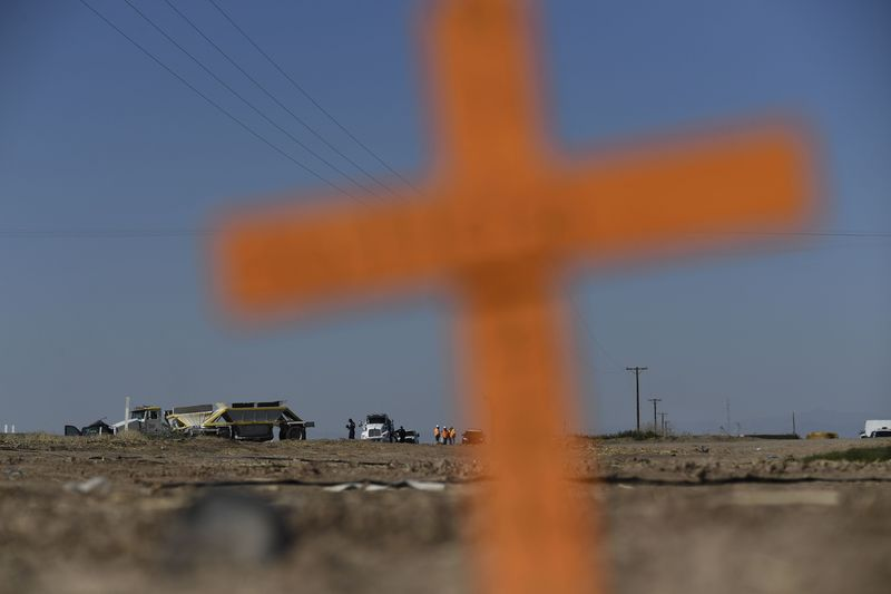 An out-of-focus cross planted in the dirt in the foreground with cleanup crews working around vehicles in the distant background.