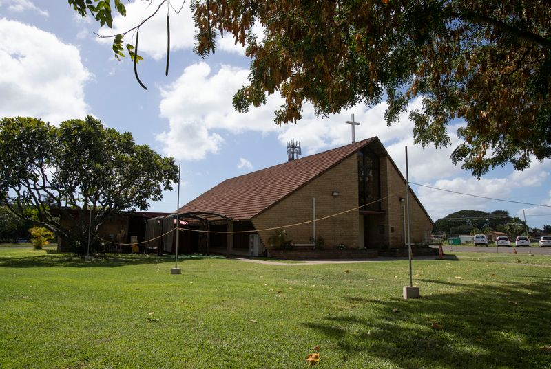 On a green lawn sits a brick building with low walls and a high, peaked roof topped by a cross.