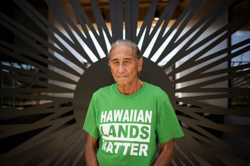 "Mike Kahikina wears a green shirt that says ""Hawaiian Lands Matter."""