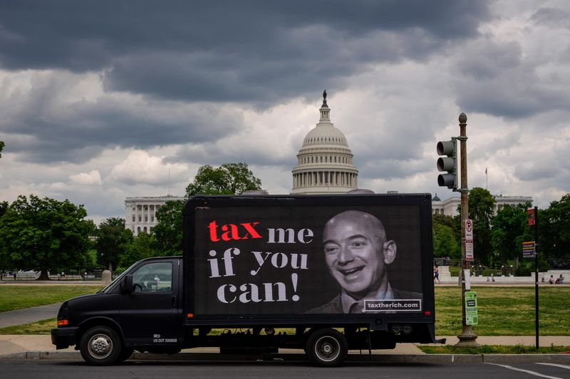 """A mobile billboard with a picture of Jeff Bezos and the caption """"tax me if you can."""""""