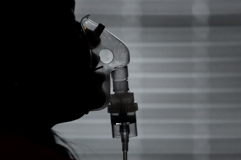In silhouette, a mouth breathes into a clear nebulizer mask.