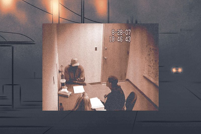 In a grainy video still, two women, seen from behind, sit across a table from a man wearing a baseball cap that throws his face into shadow.